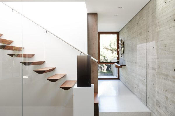 """Staircase and Wood Tread """"We didn't want panel-formed, smooth-like-glass concrete; we wanted texture,"""" Fleetwood says. A cast-resin piece by DeWain Valentine sits at the foot of the sculpted walnut stairs.  Inspiratie nieuw huis from For the Highest Green Honor, One Couple Pulls Out All the Stops"""