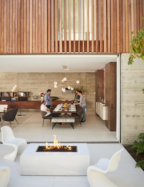 With the home's glass walls pulled open, the patio becomes an extension of the dining room. A trio of Panton chairs surround a fire pit should guests choose to congregate outside.