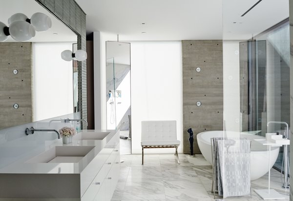 Milk-glass sconces by Lindsey Adelman are mounted on the master-bathroom mirror over a custom vanity with a Cosentino quartz-composite countertop. The freestanding Po bathtub by Boffi sits on a floor of Calacatta Gold marble.