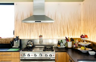 The kitchen includes backlit Bear Grass panels from 3form, a range by Capital, and a Thermador hood.