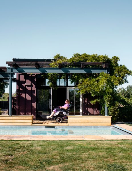 Melanie Maher sunbathes beneath the lattice of a pool house, which is clad in Cor-Ten steel.