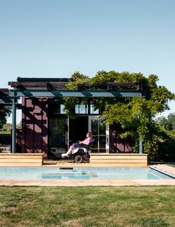 Melanie suns beneath the lattice on the porch between the pool and the pool house, which is clad in Cor-Ten steel.