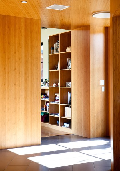 A view from the foyer into the living room, which features shelves of varying heights, shows the interplay of the bamboo-veneered plywood used throughout the house and the natural light.