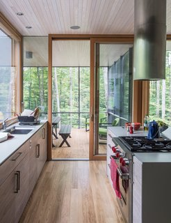 "In the kitchen, the cabinetry is walnut veneer with a weathered finish applied by cabinetmaker David Rogers. ""The process involved sanding and rubbing in stain as well as adding a clear finish,"" project architect Eero Puurunen says."