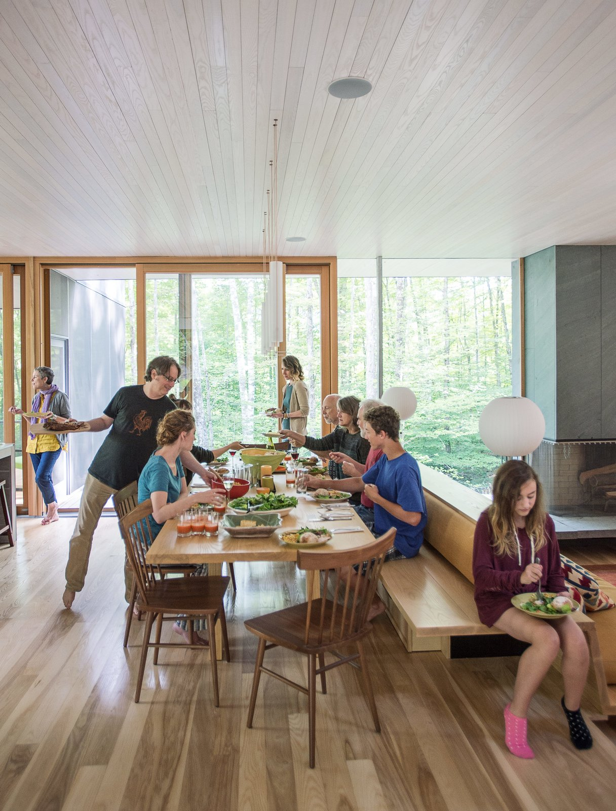 The house is about 3,000 square feet with six bedrooms, four of them on the second floor, surrounding a stairway to the large open space below where cooking, dining, game-playing, and movie-watching take place. Tagged: Dining Room, Table, Ceiling Lighting, Medium Hardwood Floor, and Recessed Lighting.  Photo 7 of 13 in It Took a Whole Family to Build This House