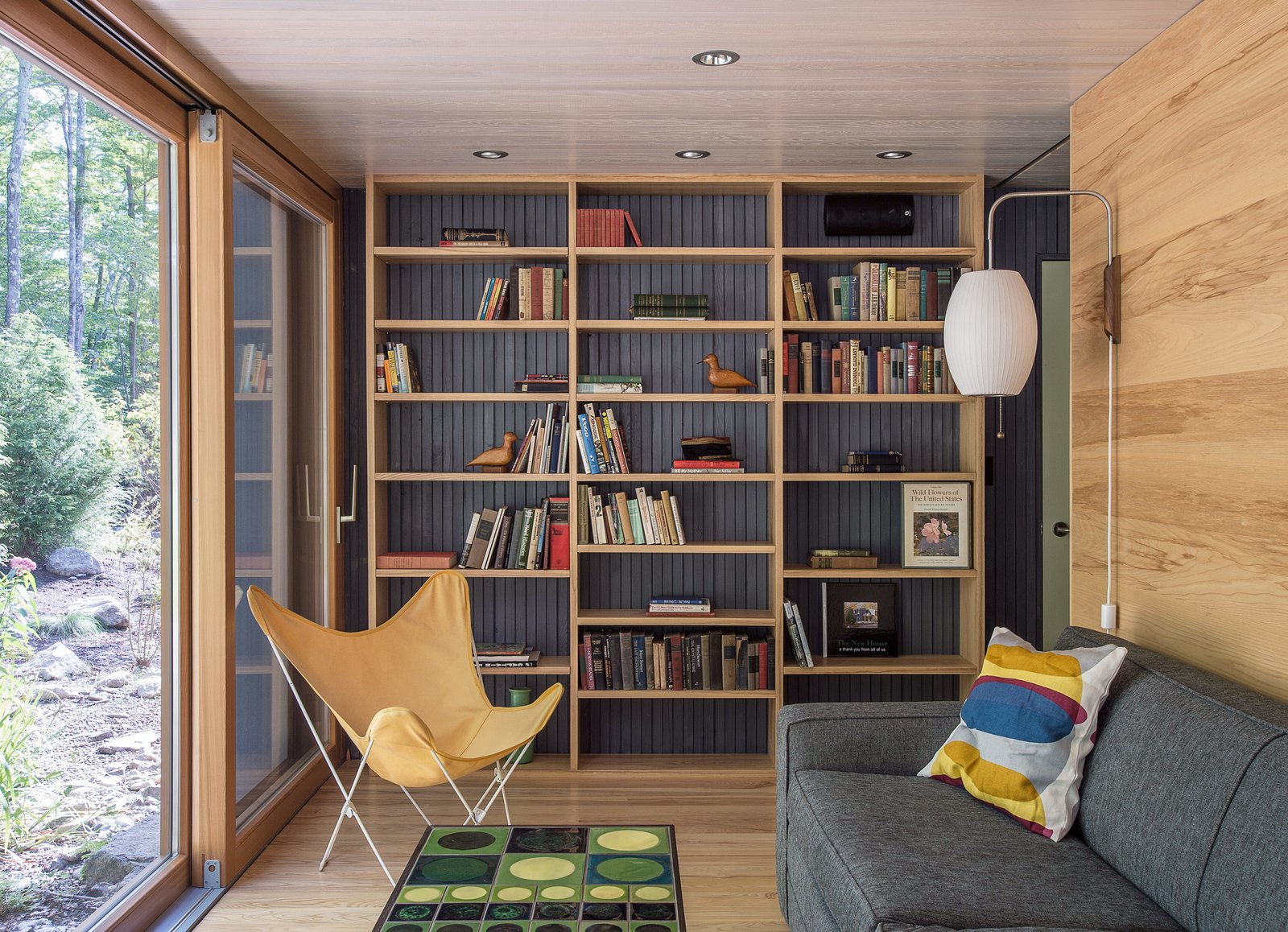 Living Room, Chair, Bookcase, Storage, Sofa, and Coffee Tables In the library, a Grant sleeper sofa by Mitchell Gold + Bob Williams is paired with a Cigar wall sconce by George Nelson.  Photo 8 of 13 in It Took a Whole Family to Build This House