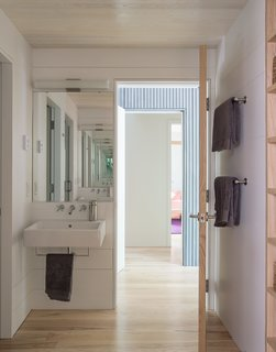 The first-floor bathroom is divided into separate functions so that it can be used by more than one person at a time: the space includes a water closet,a shower, and a larger area  with a pair of sinks. The towel racks and fixtures are from Kohler.