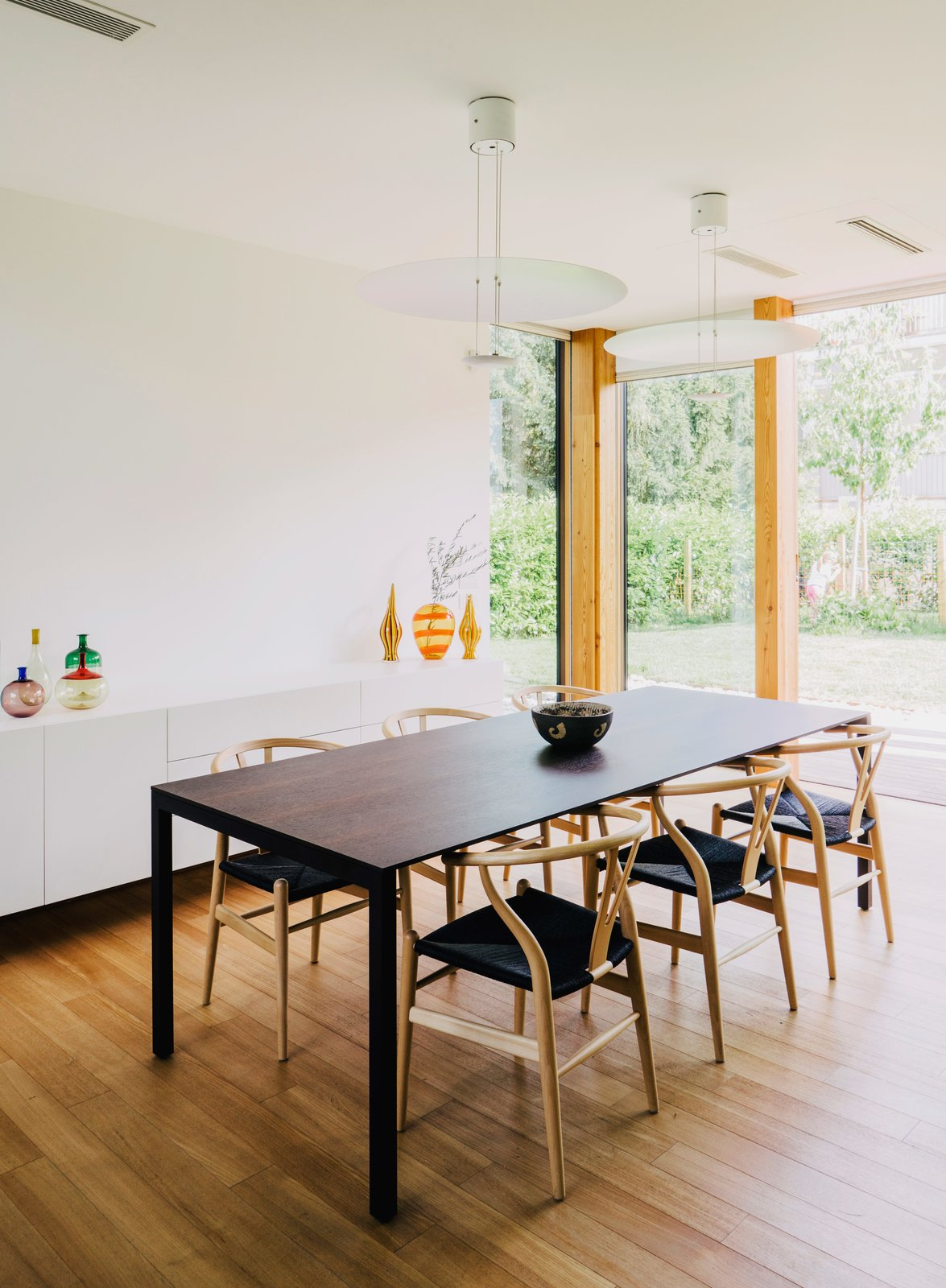 Dining Room, Table, Storage, Chair, Medium Hardwood Floor, and Pendant Lighting In the dining room, Wishbone chairs by Hans J. Wegner surround a 195 Naan table by Piero Lissoni.  In the Home from Could You Share Your Dream Home?