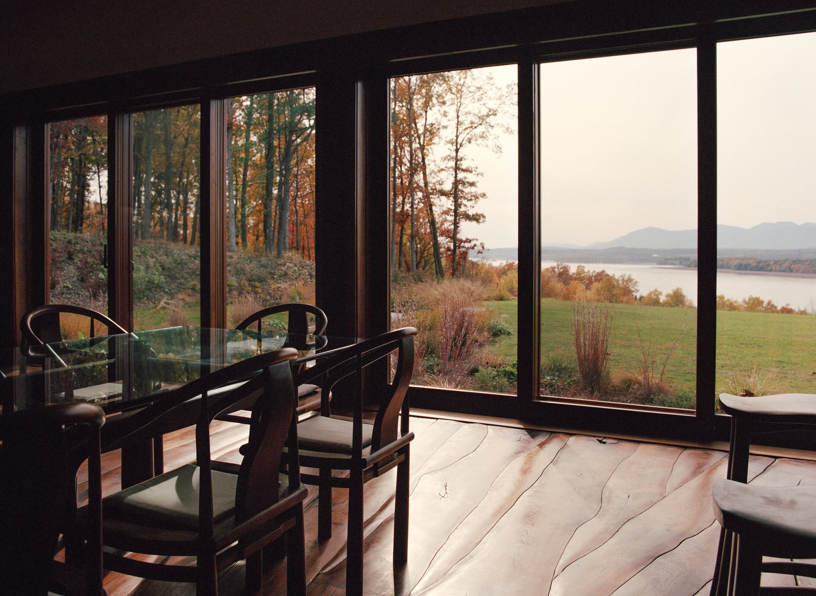 Dining Room, Chair, Table, and Medium Hardwood Floor Overlooking the Hudson River, Allan Shope's nearly 3,000-square-foot sustainable home features handmade furniture and an undulating floor, all crafted from the site's felled black walnut trees.  Photo 1 of 9 in A House Not Built for Human Beings
