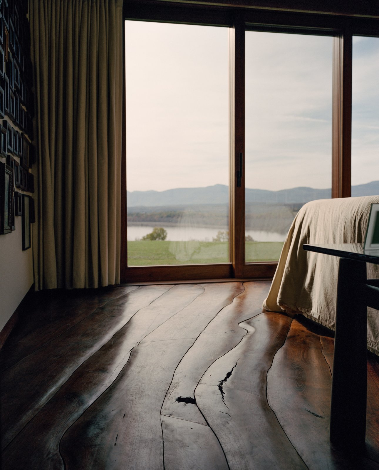Bedroom, Bed, and Medium Hardwood Floor Open to the valley, the home lets the Shopes fully experience the seasons, even the sound of the Hudson River's ice cracking in winter.  Bedroom from A House Not Built for Human Beings