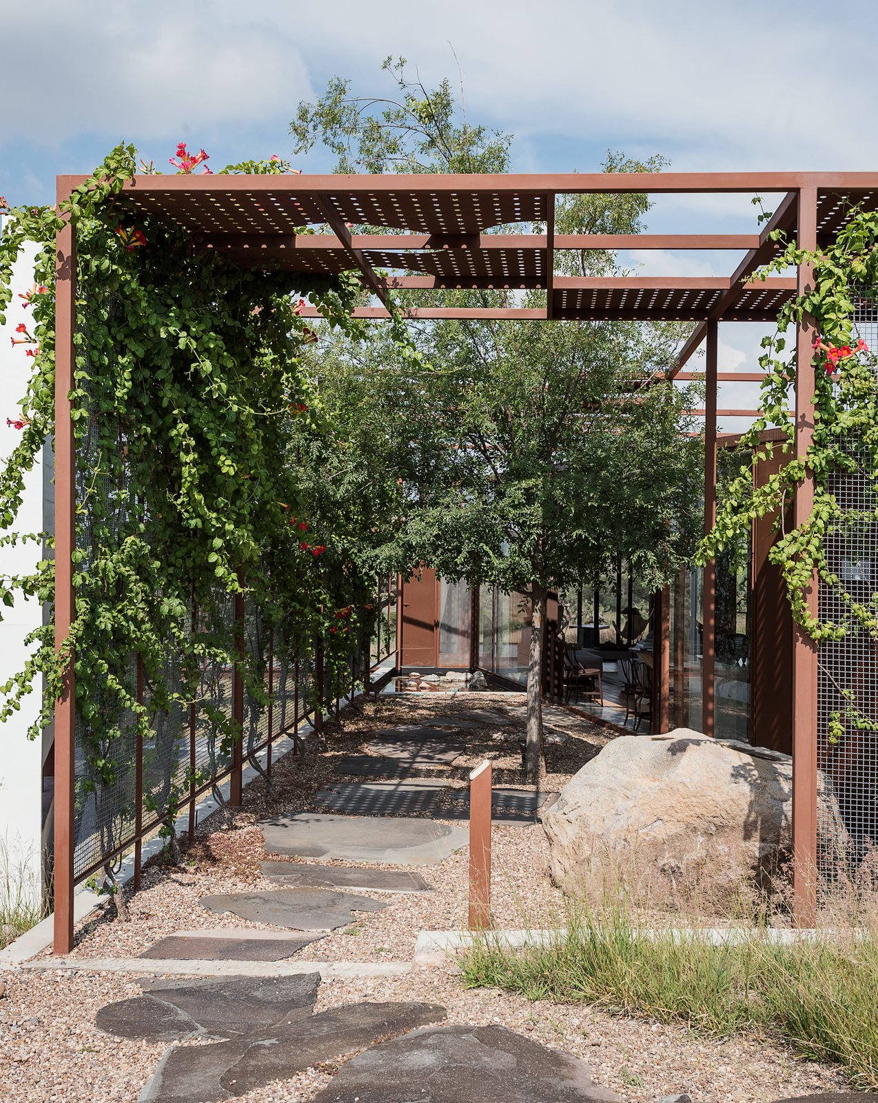 Outdoor, Walkways, and Back Yard Outside, a gridded trellis with sheet-punched panels overlays the structure and extends into the landscape, providing shade in the warm desert climate.  Photo 5 of 14 in These Separate Studios Keep a Retired Couple Happy