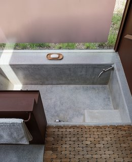 In Lida's studio, terrazzo and granite floors blend seamlessly into a sunken bath, paired with a steel storage unit and a wooden Moroccan bath mat from  Insh'ala, a local antique store.