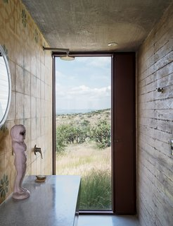Mexican encaustic tiles with a geometric floral pattern from Mosaicos Terra line the bathroom in Austin's studio, where a full-height window near the wall-mounted shower provides a view to the expansive outdoor scenery. A vintage kewpie doll sculpture sits atop the custom terrazzo-and-granite counter; the steel mirror is from Artes de México.