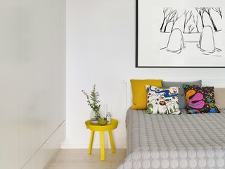 In the bedroom, a Kurt Lightner print hangs over the bed, which is covered with Hay's Mega Dot blanket and graphic pillows designed by Josef Frank for Svenskt Tenn.