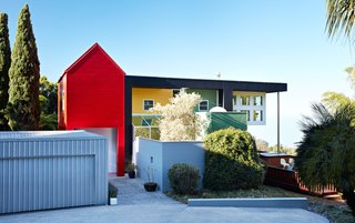 A collage of brightly colored, geometric volumes comprise the Ettore Sottsass–designed residence of Lesley Bailey and Adrian Olabuenaga, proprietors of jewelry and accessories company ACME Studio. Completed in 1997, this home is one of few private commissions designed by the Italian architect, who passed away in 2007.