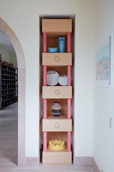 A tall custom niche displays various tabletop items Sottsass designed for brands Habitat, Memphis, Egizia, and Anthologie Quartett.