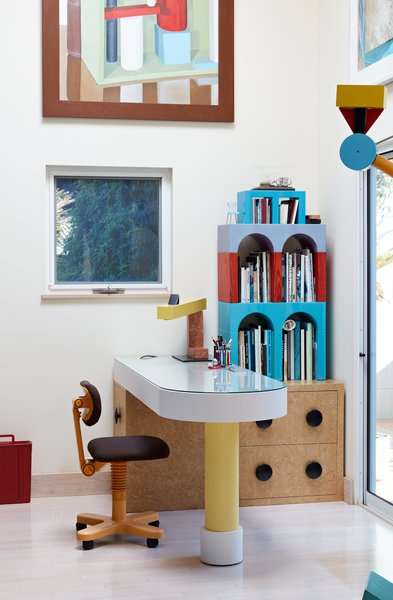 If you're looking for home office setup ideas, why not add a bit of whimsy to your workday? Giotto shelves, a Treetops floor lamp, and an Olivetti chair—all by Sottsass—furnish this fun home office. The painting is by Nathalie Du Pasquier, one of the original Memphis designers.