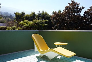 A vintage chaise lounge on the upper floor patio is one of few unnamed designs to be found throughout the residence.