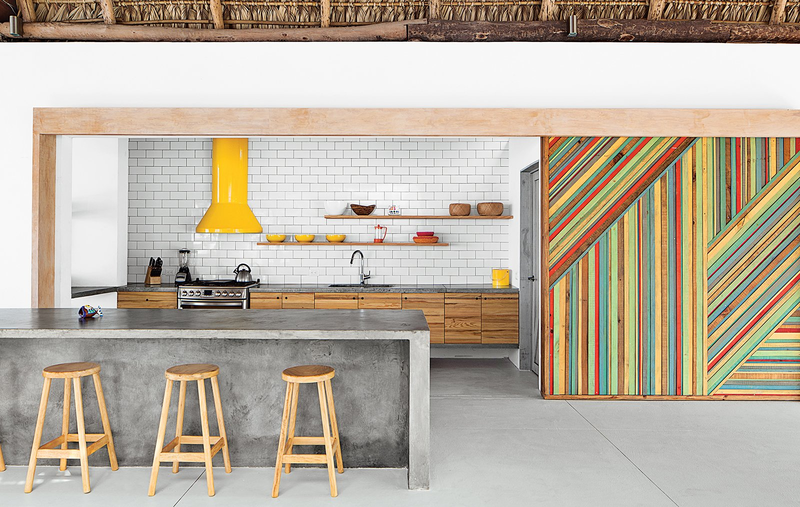 Kitchen, Concrete Counter, Wood Cabinet, Range Hood, Range, Undermount Sink, Concrete Floor, and Subway Tile Backsplashe By eliminating walls and incorporating a series of interior gardens, architect José Roberto Paredes creates an eclectic and inspired El Salvador beach house. In the kitchen, rough-hewn materials like a eucalyptus-log-and-thatch roof offset the monolithic concrete island and glossy subway tile backsplash. Claudia & Harry Washington built the vivid wooden sliding walls, which are inspired by the palm leaves that change color and create diagonal patterns in trees near the house. The bar stools were a street market discovery.  Dream Kitchens to Inspire Your Renovation by Diana Budds