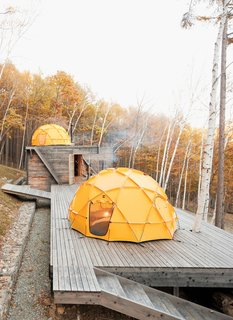 One North Face tent sits atop a deck; another caps the main building, which contains a kitchen and dining area.