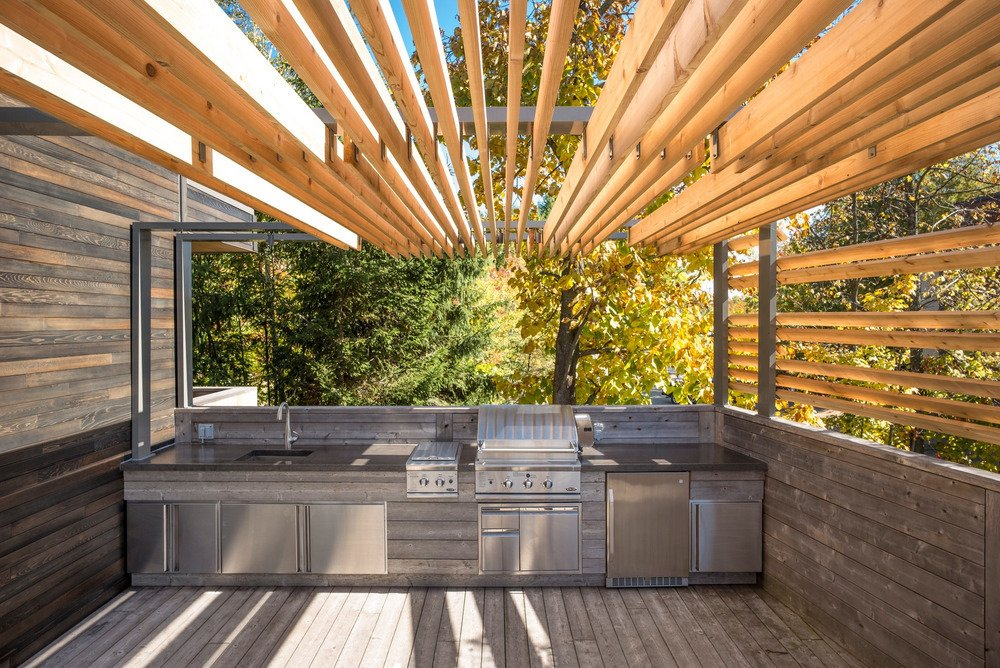 Outdoor, Large Patio, Porch, Deck, Trees, and Wood Patio, Porch, Deck At one end of the L-shaped terrace, interior designer Martine Brisson included room for a full outdoor kitchen so the family could prepare meals without stepping inside during the warmer months.  Outdoor from An Interior Designer Does the Great Outdoors