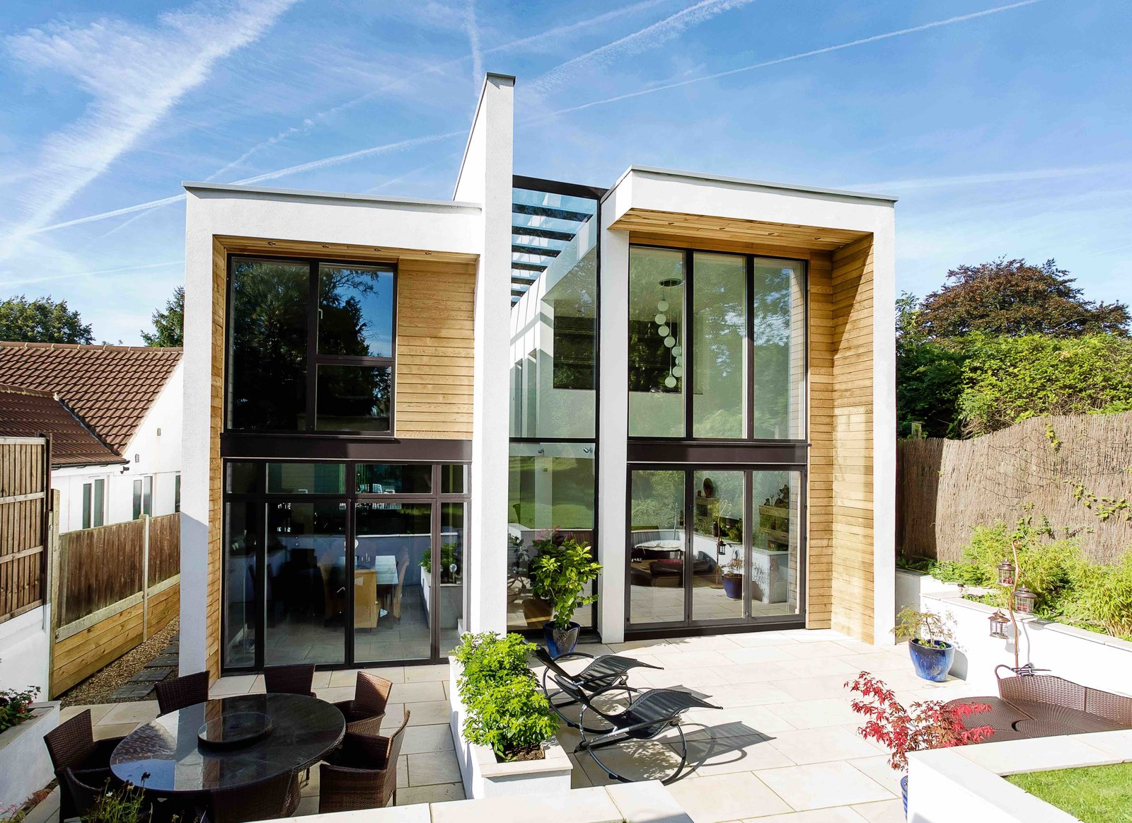 Exterior The cedar-and-glass structure rises over an expansive rear patio. Although it is larger than some of its neighbors, the home nearly matches the height line of the surrounding houses due to its flat, modern roof.  Wrap House by Luke Hopping