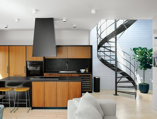 Emilie Bédard and Maria Rosa Di Ioia of EM Architecture gave Erik Rydingsvärd's top-floor apartment in a Montreal triplex a subdued, modern look that evokes his native Denmark. The range hood and satin-finished teak cabinets are by Kastella. The floors are Douglas fir and the walls are spruce, painted white.