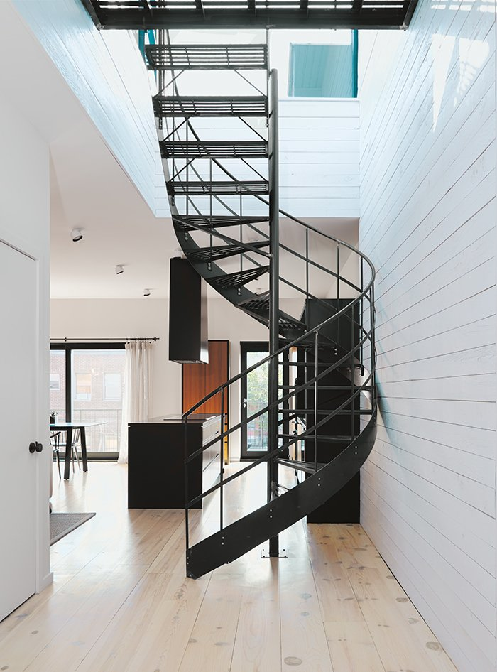Staircase, Metal Tread, and Metal Railing Di Ioia and Bédard designed the wrought-iron spiral staircase that leads to the rooftop terrace and sauna as a visual nod to Montreal's signature outdoor stairways.  Photo 6 of 14 in Scandinavian Style Revives This Montreal Home