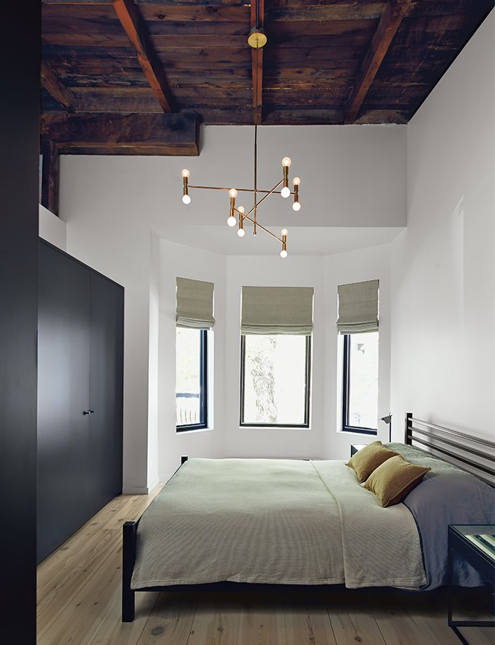 Bedroom, Bed, Night Stands, Pendant Lighting, Light Hardwood Floor, and Wardrobe The master bedroom includes an armoire by Kastella and a chandelier by Lambert & Fils. A portion of the ceiling was pared back to expose the underside of the original roof.  Photo 9 of 14 in Scandinavian Style Revives This Montreal Home