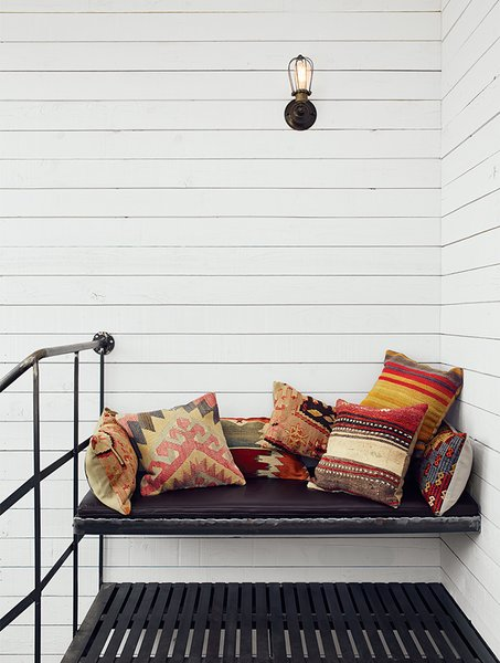 Atop the spiral staircase, a custom iron bench is festooned with Turkish throw pillows from SophiesBazaar.