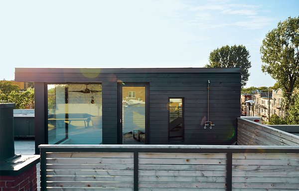 Rydingsvärd often cooks out on his terrace, which offers a view of Mount Royal. The volume housing the sauna is clad in cedar planks that were painted black. The door and windows are by Alumilex, and the custom outdoor shower is by Avantage Plus.