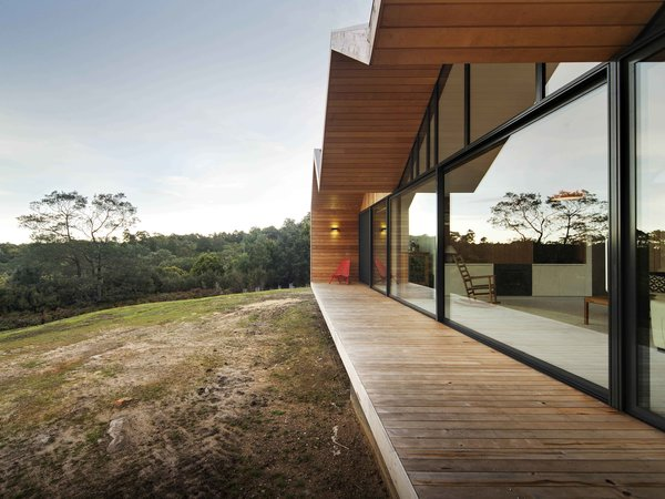 """Constructing a largely timber house in a bush fire-prone landscape wasn't easy. """"We had to negotiate with the council and building surveyor,"""" Crump explains. To solve the challenge, the architect designed an outer, protective skin for the home that's clad with metal; it pushes beyond the building envelope to provide covering for outdoor living spaces. The inset walls are lined with local shiplap Celery Top Pine."""