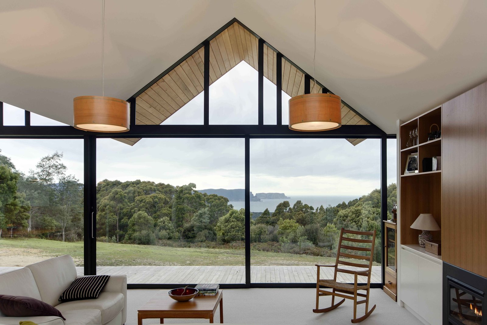 Living Room, Chair, Pendant Lighting, and Sofa A Shaker-inspired rocking chair by Hans Wegner exudes country charm in the corner of the living room.  These Modern Glass Homes Shatter Conventions by Luke Hopping from Lookout House