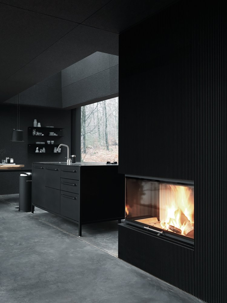 Kitchen Heating for the unit is provided by a Spartherm fireplace, with electric heating integrated into the magnesite floor. Walls are insulated with fire-tested wool felt under plywood panels.  All-Black Interiors We Love by Luke Hopping from Prefab Gets a Makeover With Danish Industrial Design