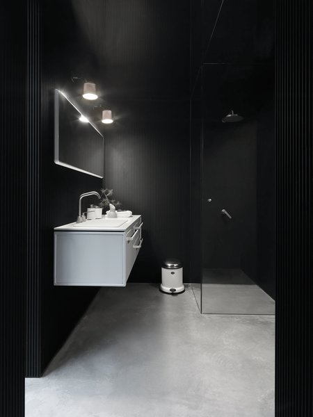 The bathroom includes a stainless steel-and-aluminum Vipp bath module with integrated sink, faucet, and Corian countertop; Vipp spot lamp; glass-walled shower with a complete set of Vipp bathroom accessories; towels; and a Duravit toilet.