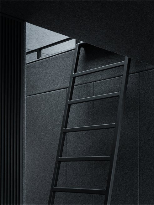 An adjustable ladder, which blends in with the walls in Vipp's signature ebony powder-coated steel, leads up to the sleeping loft.  Prefab Gets a Makeover With Danish Industrial Design  by Kelsey Keith