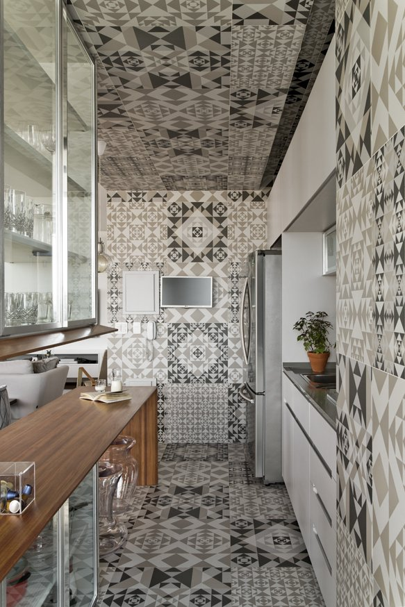 Kitchen, Cement Tile Floor, Wood Counter, Refrigerator, and Drop In Sink The graphic tile covers the floor, walls, and ceiling. The kitchen millwork was done by Inovart Carpentry.  Best Photos from This São Paulo Kitchen Makes a Case for Patterns Everywhere