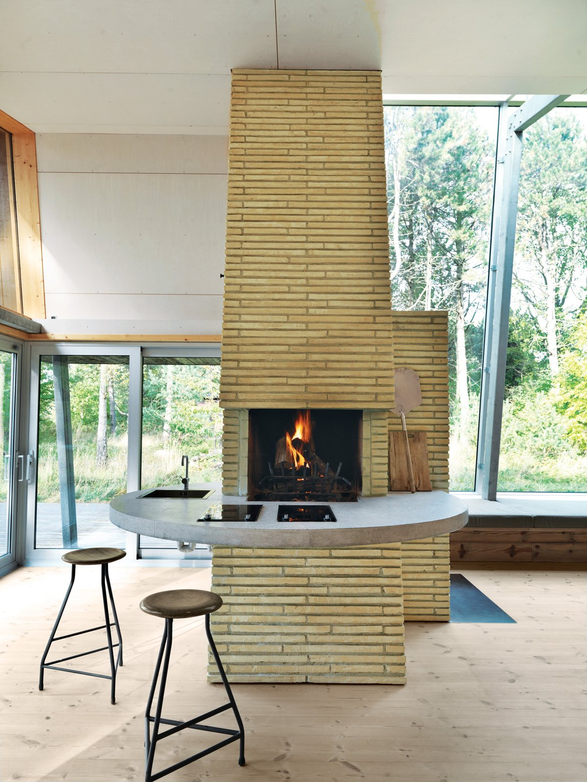 Kitchen and Concrete Counter The open-plan home's core is the towering chimney—clad in the same double-long, thin bricks that sheathe the Kolumba museum in Cologne, Germany. It holds three fireplaces, a conventional oven, and a pizza oven; all vent into three distinct flues, emerging from the chimney as their own kind of architectural statement. Inside, life revolves around the brick chimney, which the architect surrounded with a concrete counter that wraps from the kitchen to the living area. The stools are vintage.  Photo 4 of 5 in A Playful Summer Home with Some Serious Angles