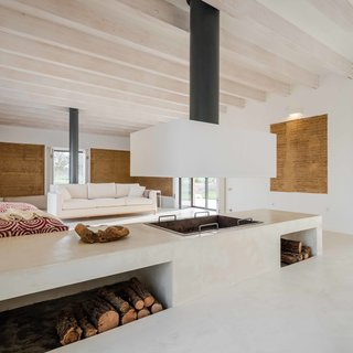 On an agricultural estate in Portugal, Blaanc Studio designed a simple retreat that does its utmost not to interfere with the scenic backdrop. The home was built with rammed earth, which is known for its thermal properties that help maintain a mild temperature all year long. A large, open fireplace with plenty of wood storage is used to warm the living area in winter.