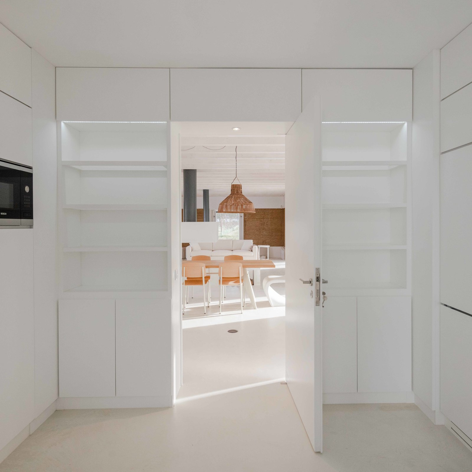 Storage, Closet, and Shelves A flat roof and all-white interior unifies the home's three volumes.  Best Storage Shelves Closet Photos from This Vineyard Hideout Is One with the Land, Literally