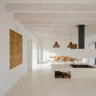 The interior showcases the roof's laminated wood beams. A Panton chair takes the seat of honor at the dining table.