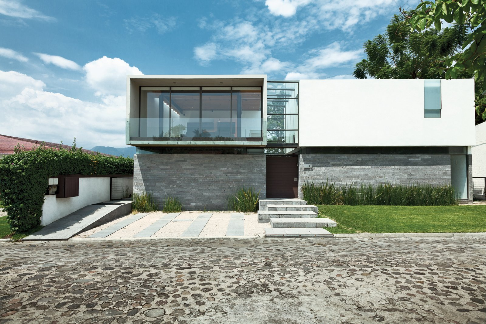 Exterior, Concrete Siding Material, Flat RoofLine, Stone Siding Material, House Building Type, Metal Siding Material, and Glass Siding Material Architect Joaquin Castillo blends inexpensive materials, the odd splurge, and a refined modernist sensibility to create an affordable weekend house for brothers Alfredo and Guillermo Oropeza. The facade is a juxtaposition of rough-hewn local stone, smooth concrete, glass, and steel—the material palette used throughout the structure.  How Boxy Would You Go? A Look at Modern Box Homes by Allie Weiss from An Affordable High-Design Vacation Home in Mexico