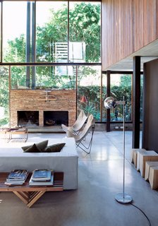 The living room resembles a Sticotti furniture showroom: The architect designed the couch, coffee tables, and stumplike stools. The fireplace is made of stacked stone from San Juan, a nearby province.
