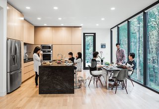 Equipped with an LG refrigerator and Thermador wall oven, the eat-in kitchen also boasts custom cabinets faced with an oak veneer and a natural stone island.