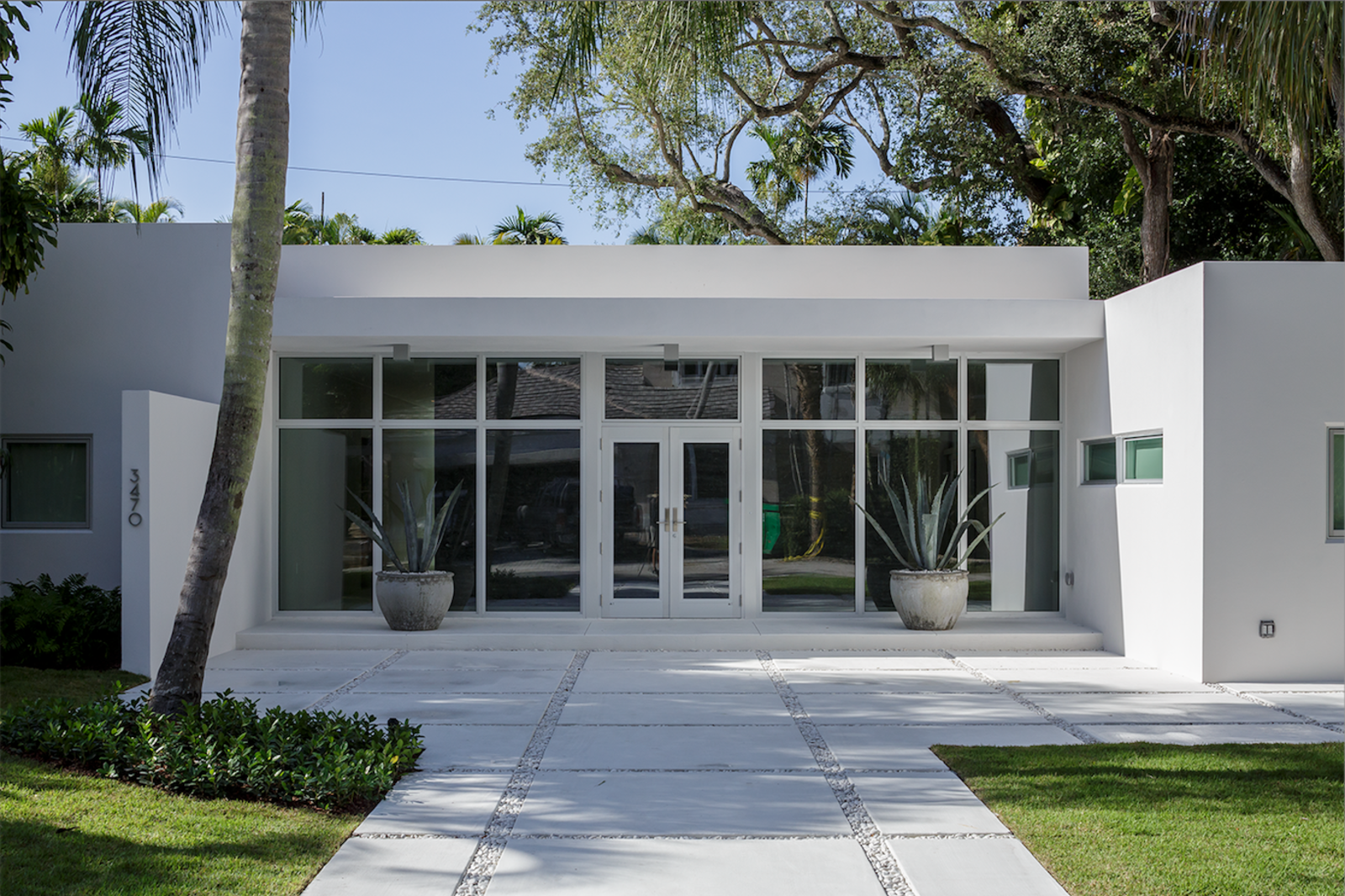The home's potential for outward expansion was limited, so new glass doors and windows were installed in a storefront configuration (a decision not common to residential construction) to provide ample natural light for the main entrance.  All-White Homes in Scorching Hot Climates by Luke Hopping