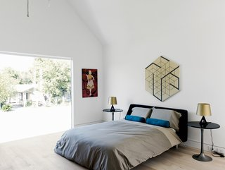 The master bedroom in Holden Shannon's unit in Houston's Row on 25th development features a Nook bed from Blu Dot, a pair of Base table lights by Tom Dixon, and a painting by artist Elva Stewart.