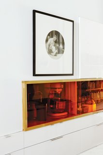 To keep vases, dishes, and small appliances handy but off the countertop, architect Tamira Sawatzky designed two niches within a wall of deep cabinets. Inset outlets supply power; butcher blocks lines all sides; and Plexiglas doors provide hits of bright orange. Plastic World, a local dealer, custom-cut the Plexiglas for the storage cubby which sits beneath a photo by artist Chris Curreri.