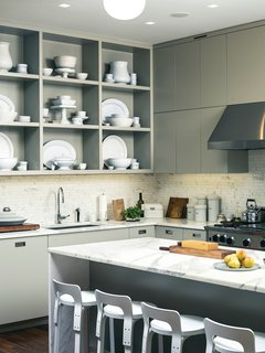 "Custom kitchen cabinets designed by Pulltab and fabricated by Maciek Winiarczyk hold mostly vintage ironstone that Geiger has found at flea markets and estate sales over the past 20 years. ""I love white,"" she says, ""because I think food always looks better on it."" She also collects vintage wooden cutting boards, shown resting against the marble tile backsplash from Stone Source."