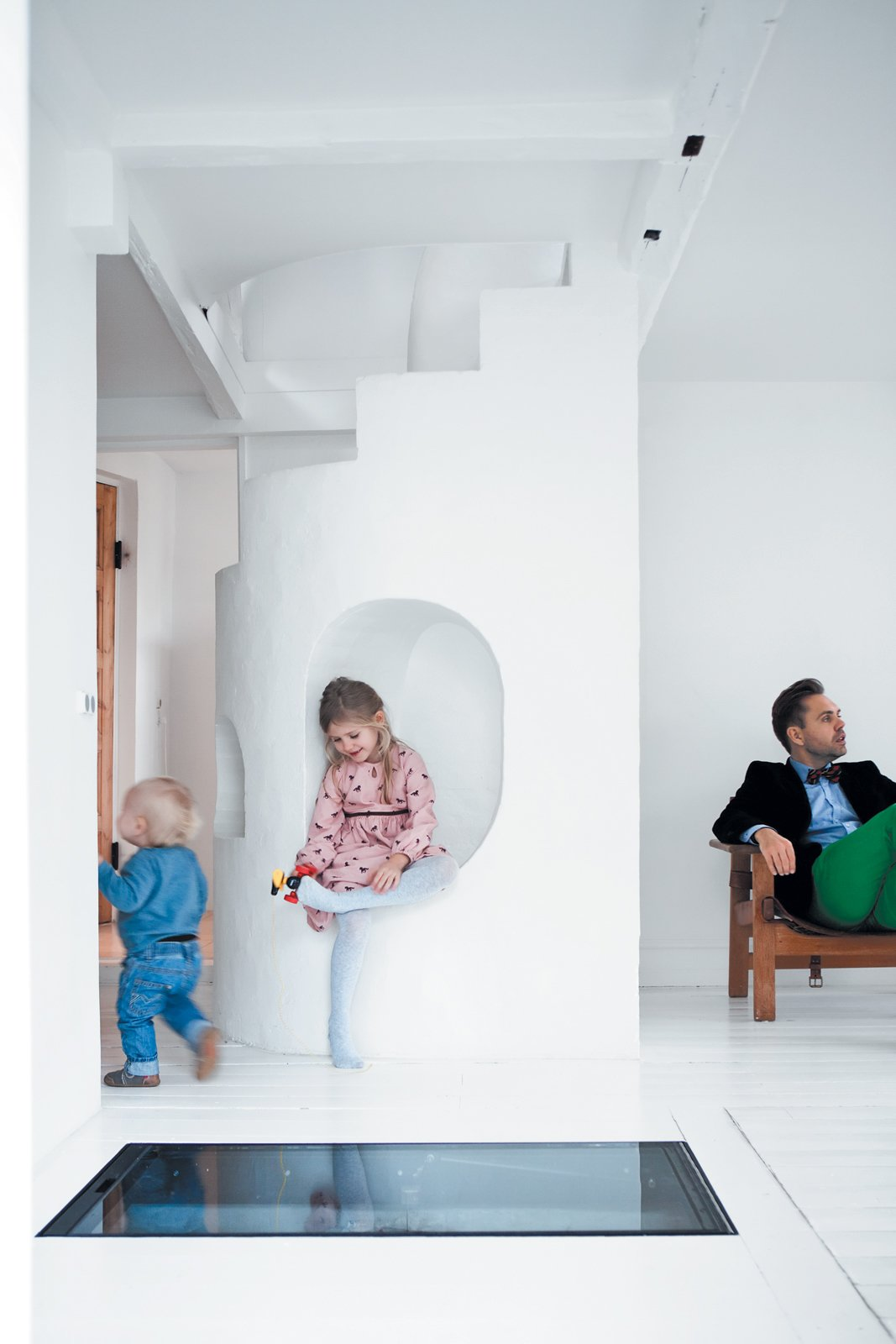 "Living Room Resident Peter Østergaard (with Maja, 6, and Carl, 20 months) and architect and photographer Jonas Bjerre-Poulsen have been best friends since they were 13, which makes for easy collaboration. Says Bjerre-Poulsen: ""There are always a lot of challenges in a renovation,   but Peter and Åsa trusted my judgment and gave me a completely free hand. Usually it's hard to push people into unconventional solutions, but Peter has   all these wild and crazy ideas."" One such idea was   to embed a transparent glass-and-iron door in   the floor, operated by a   hydraulic pump, which allows access to the subterranean wine cellar. At night, the lit-up cellar glows, lending the compact living room an increased sense   of verticality.  Photos from Light-Filled Family Home Renovation in Copenhagen"
