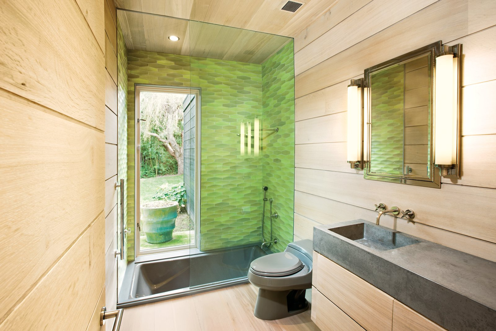 In the bathroom, Martin selected Heath Ceramics Conclave Diamond tile in citrus green for the glass-enclosed Kohler tub, which is outfitted with nickel Kallista fixtures. A matching toilet by Kohler   in the color Cashmere blends with the custom-fabricated concrete sink by Get Real Surfaces. Photo by Patrick Bernard. Tagged: Bath Room, Soaking Tub, Enclosed Shower, Light Hardwood Floor, and Concrete Counter.  Mid Century from A Sustainable Mid-Century Beach House